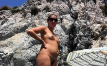 Spy cam shot of a hot nudist babe tanning on the beach